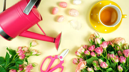 Welcoming Spring pink and yellow theme concept flat lay tea break with roses and gardening accessories. 写真素材