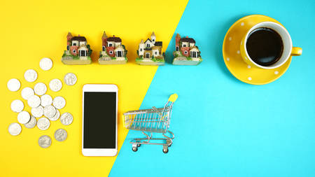 E-commerce real estate shopping, planning and financing for houses concept with miniature shopping cart and desk accessories with copy space.