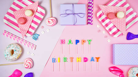 Colorful pink theme birthday party flat lay with party food, balloons, lollipops and gifts, candles spelling Happy Birthday