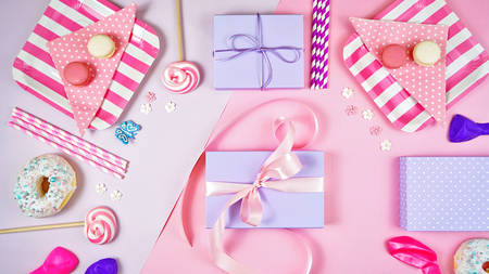 Colorful pink theme birthday party flat lay with party food, balloons and lollipops, tying ribbon around gift in centre.