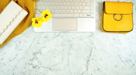 Modern desk flat lay overhead with touchscreen laptop and yellow accessories, copy space. 写真素材