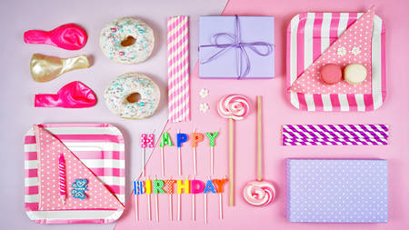 Colorful pink theme birthday party flat lay with party food, balloons, lollipops and gifts, organised flat lay layout.