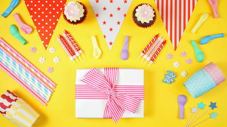 Colorful birthday party flat lay with party food, balloons, decorations and gifts on yellow