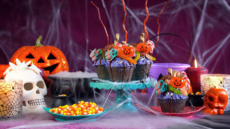 Happy Halloween drip cake style cupcakes with lollipops and candy in party table setting, with copy space