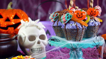 Happy Halloween  drip cake style cupcakes with lollipops and candy in party table setting, close up.