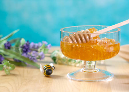 Raw honeycomb with liquid honey in glass jar with lavendar on blue background.