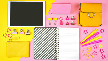 Back to school pink and yellow teens theme concept flatlay with tablet device, notebook, stationery and accessories.