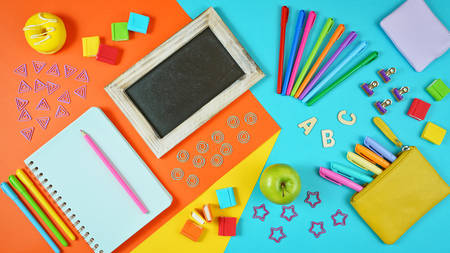 Back to school colorful kids theme concept flat lay with blackboard, notebook, stationery and apple for the teacher.