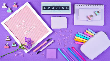 Back to school purple teens theme concept flat lay with pink notice board, stationery and accessories.