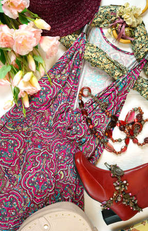 On-trend Boho Chic style fashion layout flat lay with red pink floral summer dress and accessories.