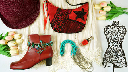 On-trend Boho Chic style fashion layout flat lay with white lace dress and red accessories.