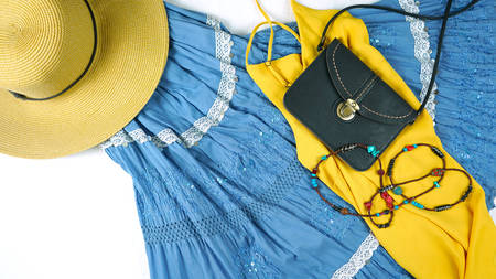 On-trend Boho Chic style fashion layout flat lay with blue and yellow theme bohemian skirt, sandals, and accessories.