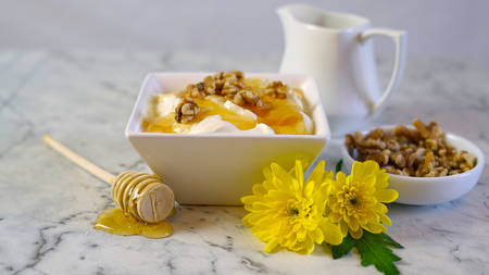 Greek yoghurt served with natural raw honey and walnuts on white marble table background. Imagens