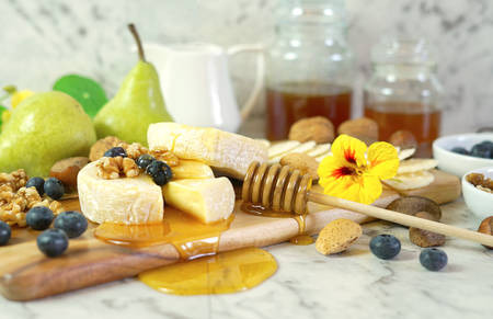 Camembert and brie cheese board with honey, fruit and nuts. Imagens