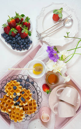Modern blush pink breakfast tray with waffles, honey and fruit.