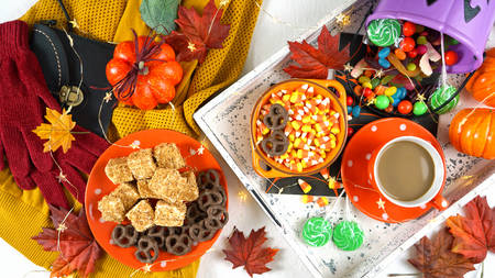 Halloween concept of relaxing with coffee and a tray of candy and treats, flat lay overhead. Imagens