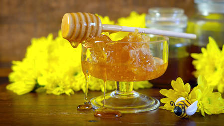 Raw honeycomb with liquid honey in glass bowl with serving dipper and yellow daisies on rustic dark wood Imagens