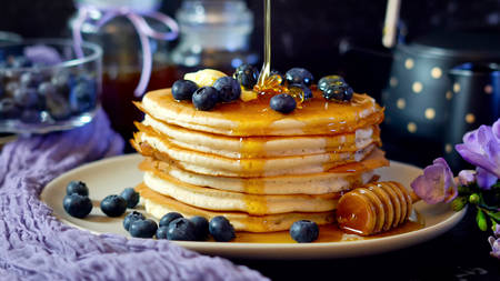 Breakfast pancake stack served with blueberries and honey.