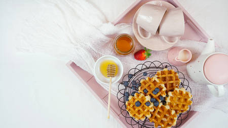 Modern blush pink breakfast tray with waffles, honey and fruit with copy space. Imagens