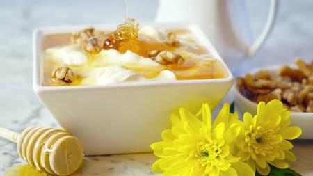 Creamy greek style yoghurt served with honey and walnuts, closeup.
