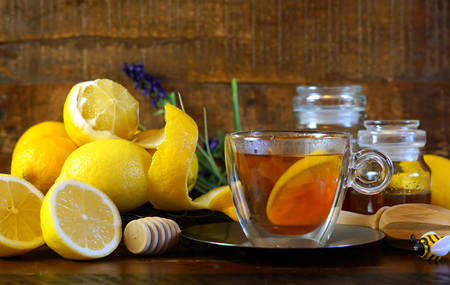 Traditional honey and lemons served with a cup of tea on rustic wood