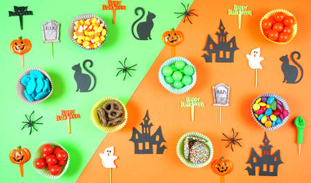 Halloween candy and paper flat lay on bright modern orange and green background.