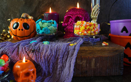 Halloween party table with candy, pumpkins and skeleton candles.