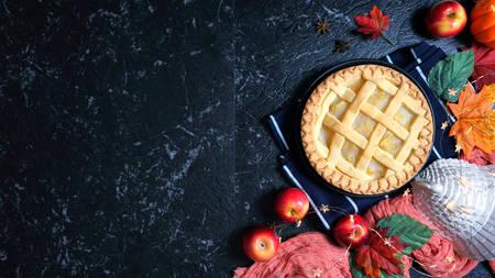 Tartes aux pommes et citrouilles de Thanksgiving sur fond de marbre foncé.