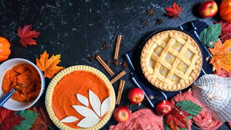 Thanksgiving apple and pumpkin pies on dark marble background.
