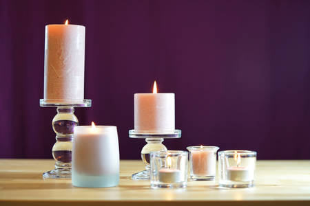 Aromatherapy composition with pink candles on table against purple background Imagens
