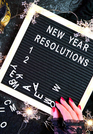 New Years Eve resolutions letter board and black and gold party decorations. Stock Photo