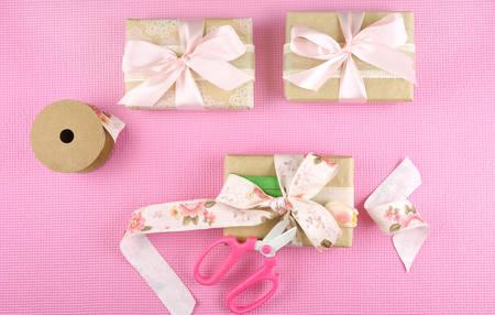 用牛皮纸和粉色丝带包裹的礼物放在头顶上。
