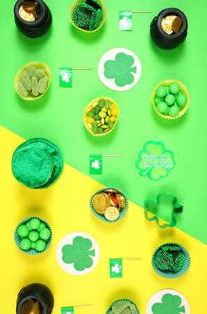 St Patricks Day flat lay with chocolate coins, leprechaun hat and shamrocks.