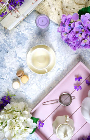 Relaxing at home with hygge style lavender tea and tray, old books, and cozy sweater on white textured background. Top view creative composition flat lay vertical orientation.