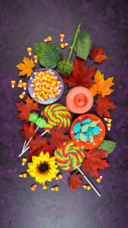 Happy Halloween Trick or Treat theme desktop with candy and lollipops, autumn leaves on stylish purple textured background. Top view blog hero header creative composition flat lay. Stock fotó