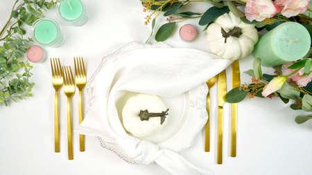 Happy Thanksgiving table setting with modern white pumpkins centerpiece. Foto de archivo