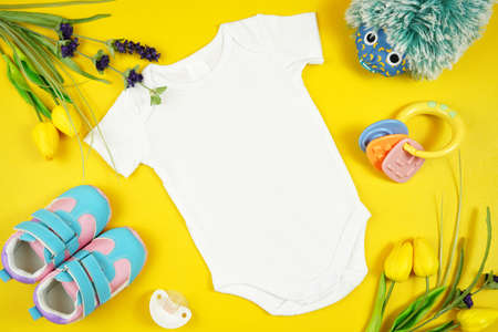 Springtime baby apparel flatlay top view on yellow table. Mock up.