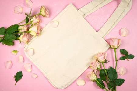 Mother's Day Valentine wedding birthday feminine theme canvas tote bag styled with blush pink roses against a pink textured background. Mockup. Copy space.