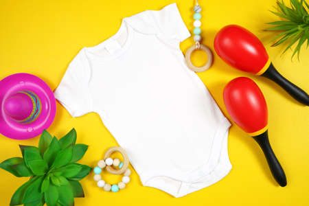 Cinco de Mayo baby romper flatlay on a festive yellow table background.