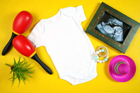 Cinco de Mayo baby romper with sonogram flatlay on a yellow table background
