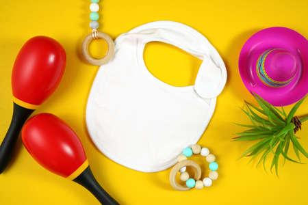 Cinco de Mayo baby bib flatlay on a festive yellow table background