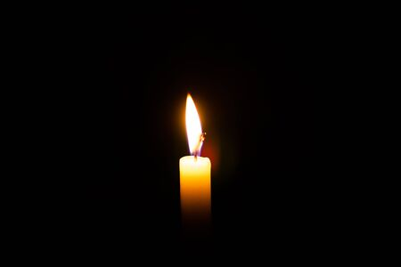 Kerzenflamme gegen isoliert auf schwarz