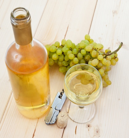 A bottle of white wine, grapes and a glass on the table photo