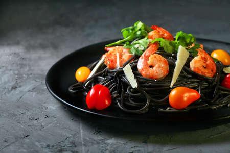 spaghetti negro, italian black pasta with seafood, with shrimp, cheese, tomato, horizontal, black background
