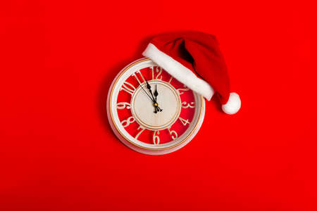 clock on a red background in a hat of Santa Claus, new year, christmas, wallpaper, horizontal
