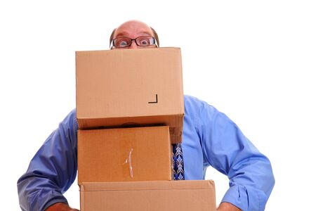 Zakenman in paniek omdat hij gevaarlijk zware dozen vervoert, probeert ze voor zich uit te balanceren zonder de dozen omver te werpen. Stockfoto