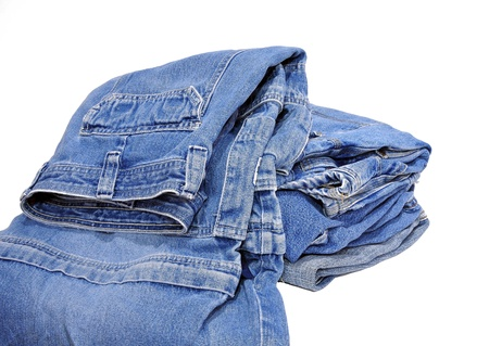 Stack of folded jeans with one pair partially unfolded photo