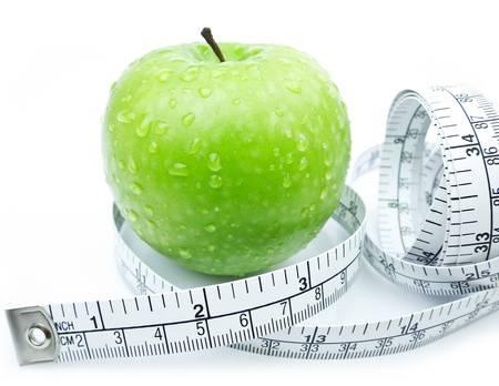 Verde mela con nastro di misura su sfondo bianco Archivio Fotografico