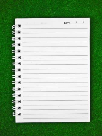 Notebook paper on green background photo