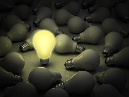 Business concept, one glowing light bulb standing out from the unlit incandescent bulbs photo